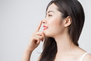 Young beautiful Asian woman with smiley face and red lips touching her nose